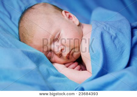 newborn boy sleeping under blue sheet