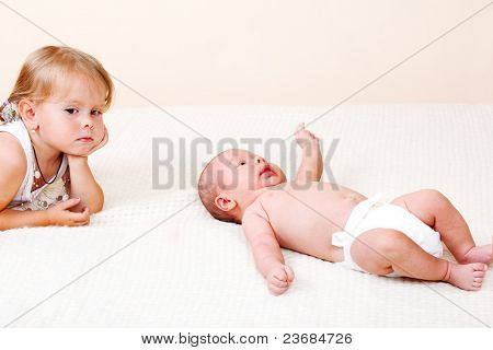 Sad toddler girl and newborn baby lying on bed