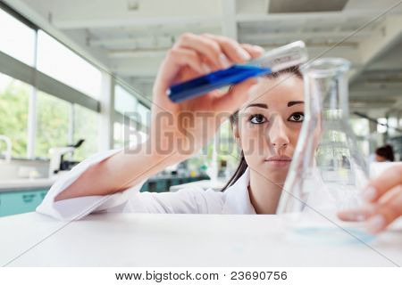 Focused science student pouring liquid in an Erlenmeyer flask