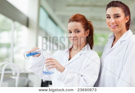 Scientists pouring blue liquid in an Erlenmeyer flask in a laboratory