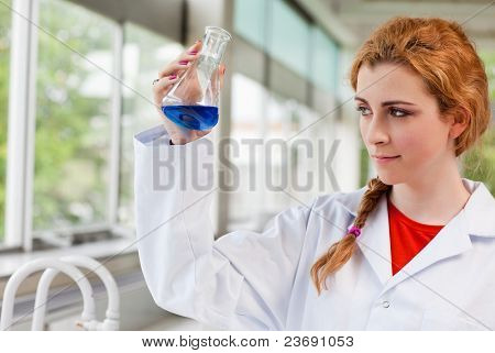 Chemist looking at a blue liquid in an Erlenmeyer flask