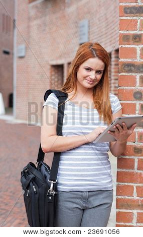 Portrait of a young student working with a tablet computer outside a building
