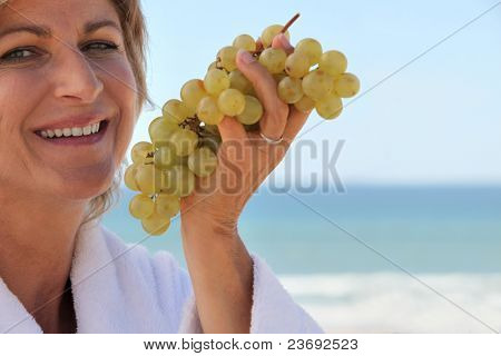 Woman eating a bunch of grapes by the sea