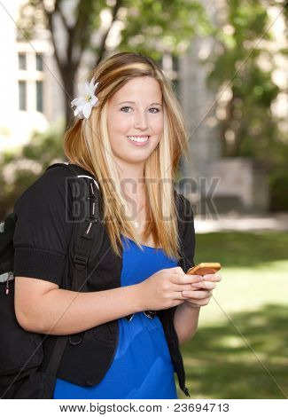 Young pretty college girl texting on phone