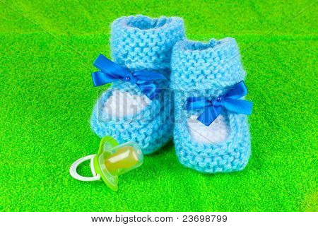 Blue baby booties and pacifier on green background