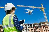 Drone inspection. Operator inspecting construction building site flying with drone poster
