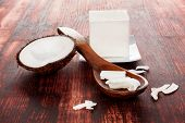 Healthy Coconut Oil For Hair. Coconut Flakes In Spoon On Wooden Table. Hard Coconut Oil Cube. poster