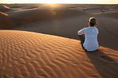 Woman Sitting Alone At Sunset Among The Red Sand Dunes Of The Wahiba Desert In Oman poster