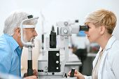 Oculist Cheking Patients Vision With Medical Equipment. poster