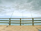 Fishers Rods Against Handrail Of Wooden Bridge.  Fishing On Harbor Mole. Overcast Day, With The Hidd poster