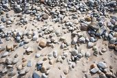 stock photo of profusion  - Profusion of colorful rounded beach stones on a background of sand - JPG