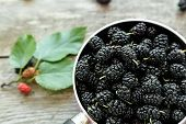 Black Mulberry Berries In A Pink Pot On A Wooden Table. In The Foreground Are Mulberry Berries And S poster