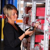 stock photo of factory-worker  - worker scans pallets and boxes in the warehouse - JPG