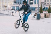 The Teen Does Tricks On The Bmx. Bmx Cyclist Rides A Bike Around The Park And Makes Tricks. Bmx Conc poster