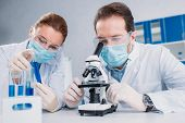 Researchers In White Coats And Medical Masks Working With Reagents Together In Lab poster