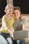 Affectionate Couple Watching Something At Laptop At Home poster