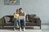 Affectionate Couple Watching Movie At Laptop At Home poster