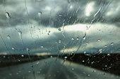 Rain Drops On A Car Windshield. Rainy Day View Through A Car Window. Rainy Season Concept. poster