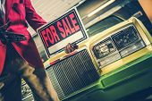 Car For Sale Sign In A Hand Of Car Seller. Automotive Dealership Theme. poster
