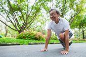 Old Senior Man Runner In A Starting Position Preparing To Run. Elderly  Ready For Exercise Jogging.  poster