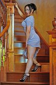 foto of upper thigh  - A relaxed beautiful Asian woman wraps her hands around the hand rail on a solid wood stair casing as she pauses and looks back while holder her dress revealing her upper thigh - JPG