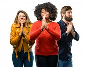 Group of three young men and women with hands together in praying gesture, expressing hope and pleas poster