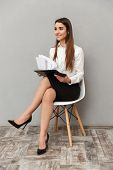 Full length image of business woman with long brown hair in formal wear sitting on chair and looking poster