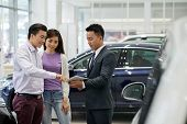 Car Dealership Salesman Showing Information On Tablet Computer To Customers poster