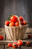 Small Red Cherry Tomatoes  In A Small Wicker Basket  On Wooden Table. Healthy Organic Food. Tomato H poster