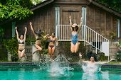 Beautiful Young Women In Swimwear Jumping In Swimming Pool At Tropical Resort poster