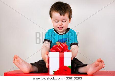 Happy toddler boy opening gift box