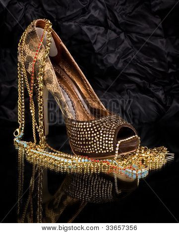 Sexy fashionable shoe with golden jewelry on background