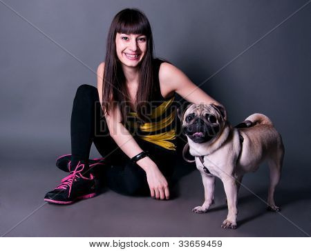 Pretty Sport Girl With Pug Dog In Studio