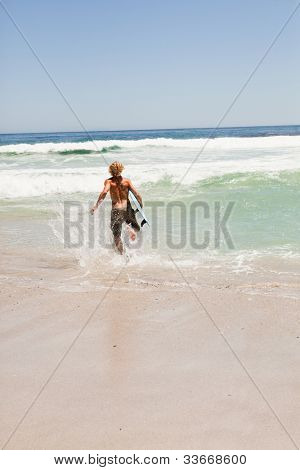 Young blonde man running in the water with his surfboard