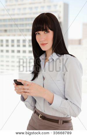 eine geschäftsfrau sieht vor, wie sie einen Text von ihrem Handy sendet