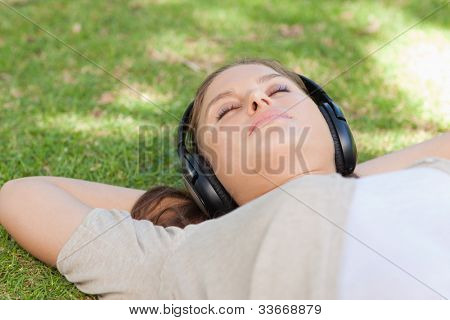 Relaxed young woman lying on the lawn enjoying music