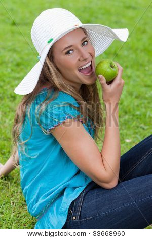 Happy young girl eating a delicious green apple while sitting down in the countryside