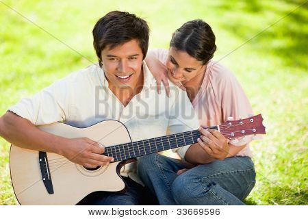 Woman putting her hand on her smiling friends shoulder while he plays the guitar as they both sit on the grass