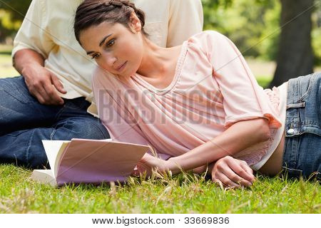 Woman reading a book while lying down next to her friend who is sitting down on the grass