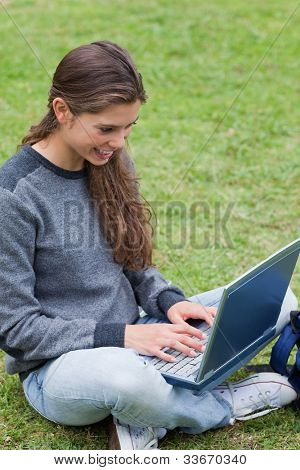 Smiling student typing on her laptop while sitting cross-legged on the grass in a park