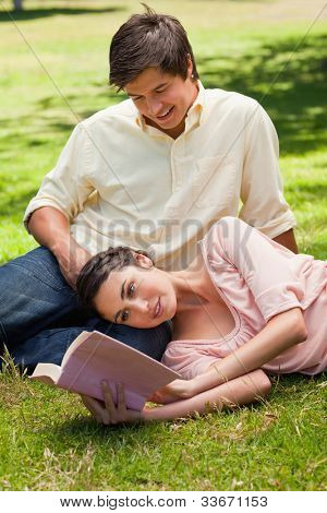 Woman lying on her side while reading a book as her friend looks at her as he sits on the grass