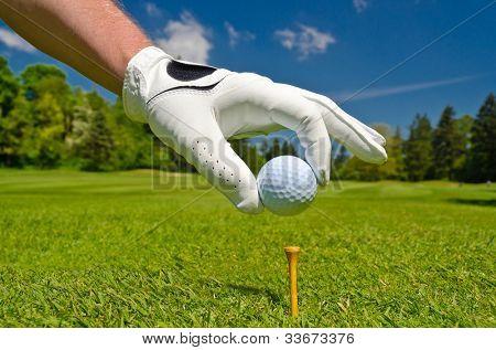 mão, colocando a bola de golfe no tee sobre belo campo de golfe com céu azul