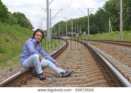 Man Sitting On The Railroad Tracks