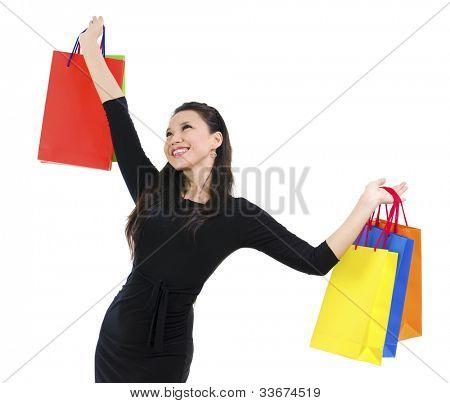Happy shopper holding shopping bag high isolated on white background