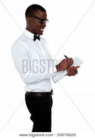 African Employee Writing On Clipboard