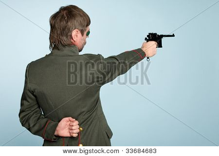Man in the uniform of a military officer fires a gun.