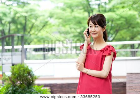 Beautiful young woman using a moblie phone. Portrait of asian.
