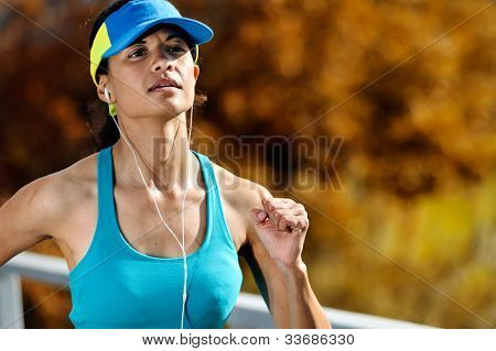 portrait of an athlete running outdoors with headphones and autumn leaves. wellness, fitness exercise woman training