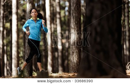 runner trail running training in forest outdoors, healthy fitness wellness athlete portrait