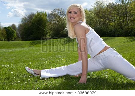 Young attractive blonde stretching outside on a field